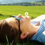 Entspanntes Ich = Gesundes Ich - Frau liegt auf Wiese mit Gänseblümchen im Mund